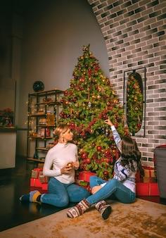 Две красивые женщины крупным планом под праздничной елкой в помещении с коробками подарков. новогоднее фото