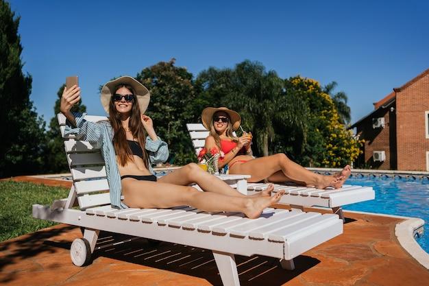 プールの近くでスマートフォンで自分撮り写真を撮る帽子をかぶった2人のきれいな女性