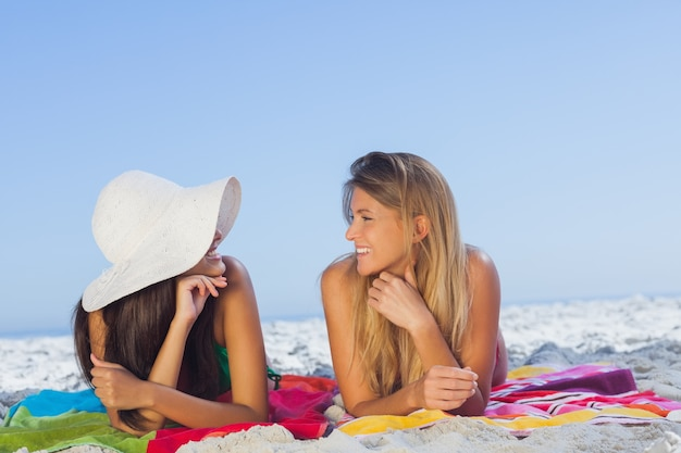 Two pretty women lying on the sand