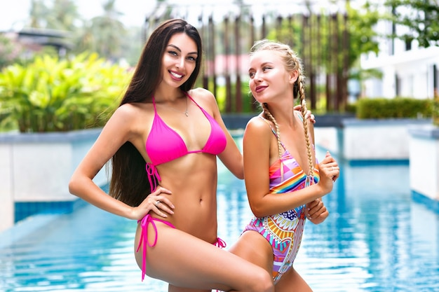 Две красивые женщины в модных ярких бикини позируют возле бассейна в роскошном тропическом отеле