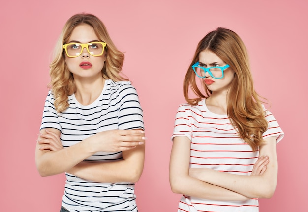 Two pretty women in sunglasses striped tshirts summer friends chatting