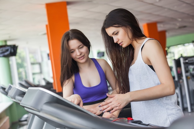 Two pretty women trying to turn on the treadmill in the gym indoors. beautiful girls training in the gym. a group of the fitness begginers trying to train