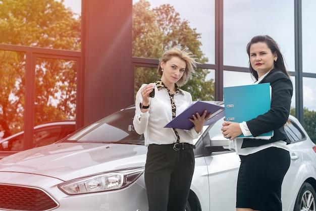 Две красивые женщины с папками, стоящие возле новой машины. проверяют какие-то документы в папках
