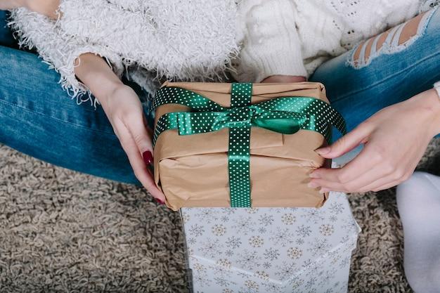 クリスマスのためのギフトを持つ2つのきれいな女性、ビューを閉じる