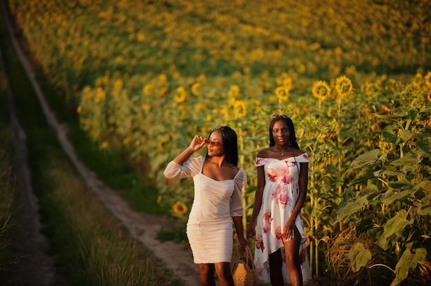 Two pretty young black friends woman wear summer dress pose in a sunflower field.