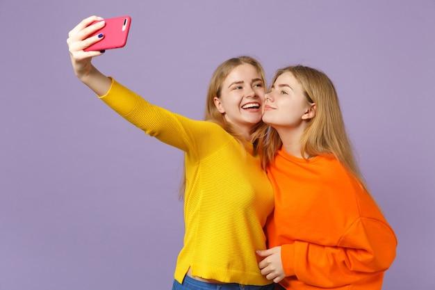 パステルバイオレットブルーの壁に隔離された携帯電話でselfieショットをしているカラフルな服を着た2人のかなり若いブロンドの双子の姉妹の女の子。人々の家族のライフスタイルの概念。