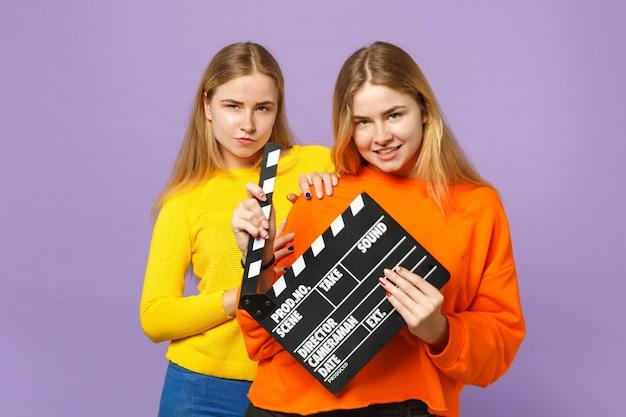 보라색 파란색 벽에 절연 clapperboard 만들기 클래식 블랙 영화를 들고 화려한 옷을 입고 두 꽤 젊은 금발 쌍둥이 자매 여자. 사람들이 가족 라이프 스타일 개념.