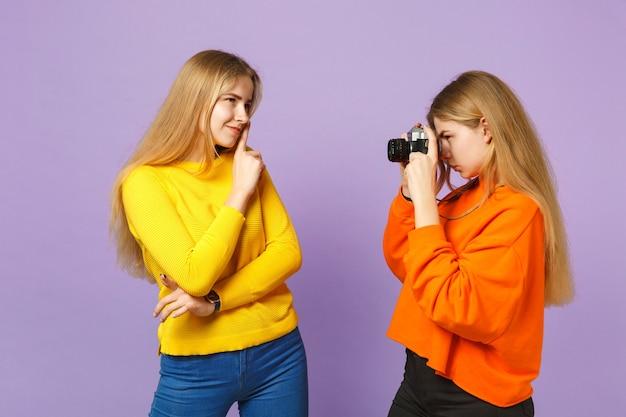 Две симпатичные молодые блондинки сестры-близнецы девушки в красочной одежде фотографируют на ретро-винтажную фотокамеру, изолированную на фиолетовой синей стене. концепция семейного образа жизни людей.