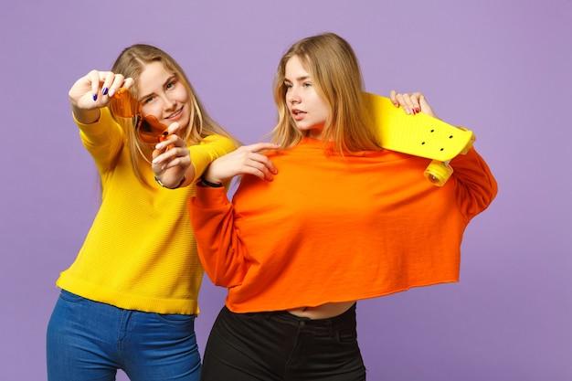 鮮やかな服を着た2人のかなり若い金髪の双子の姉妹の女の子、パステルバイオレットブルーの壁に分離された黄色のスケートボードを保持しているハートの眼鏡。人々の家族のライフスタイルの概念。