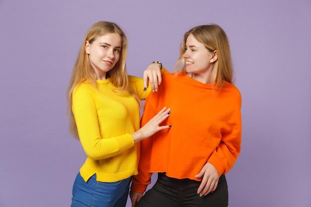 두 예쁜 젊은 금발 쌍둥이 자매 여자 서, 파스텔 바이올렛 파란색 벽에 고립 된 서로보고 생생한 화려한 옷을 입고. 사람들이 가족 라이프 스타일 개념.