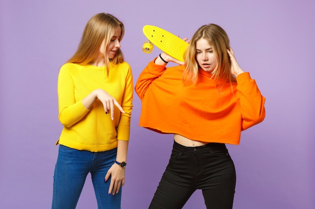 Two pretty young blonde twins sisters girls in vivid clothes pointing index finger, holding yellow skateboard isolated on violet blue wall. people family lifestyle concept.