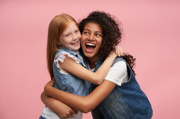 ピンクの上に立って、一緒に楽しい時間を過ごし、広い笑顔で楽しく笑っている間、家族を着ている2人のかなり若い陽気な女の子が見えます