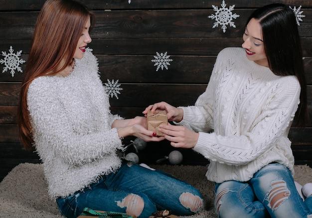 Две симпатичные молодые забавные женщины-друзья улыбаются и веселятся, держа в руках праздничные подарки, готовые к празднованию.