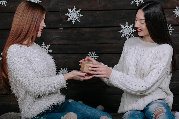 Due amici di donne divertenti abbastanza giovani sorridenti e divertendosi, che tengono i regali di festa, pronti per la celebrazione.