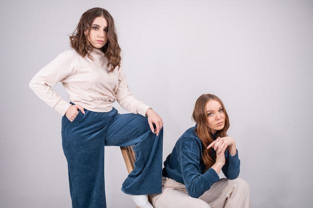 Две довольно молодые подруги в стильной повседневной одежде позируют