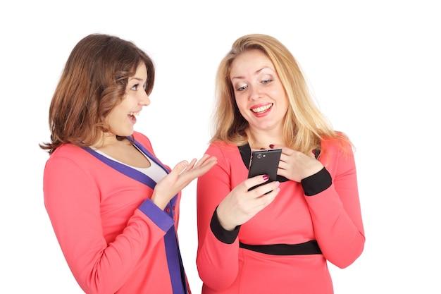 Две красивые молодые девушки выбирают товары по мобильному телефону в интернет-магазине