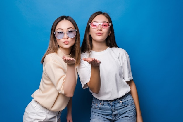 Two pretty young girls dressed in summer clothes standing and sending kiss isolated over blue wall