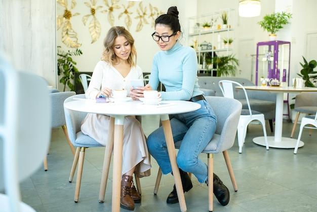 Две симпатичные молодые межкультурные женщины просматривают страницы интернет-магазина, прокручивая смартфон за столиком в кафе