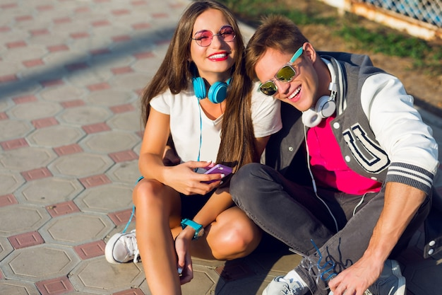 Two pretty young modern teenagers posing outdoor in stylish casual outfit