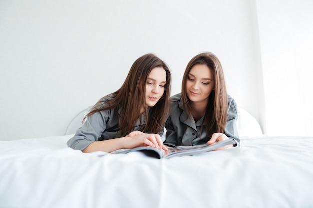 Две симпатичные молодые сестры-близнецы лежат и читают журнал в спальне