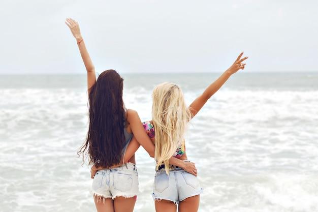 Due belle giovani surfiste amiche delle migliori amiche che si divertono in vacanza, mini shorts in denim.