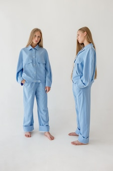Two pretty young twin sisters with long blond hair posing on white background in oversize clothes. fashion photoshoot