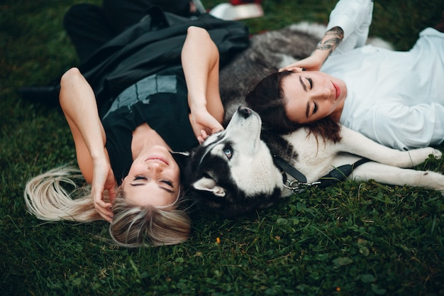 Two pretty young woman laying with husky dog on the grass