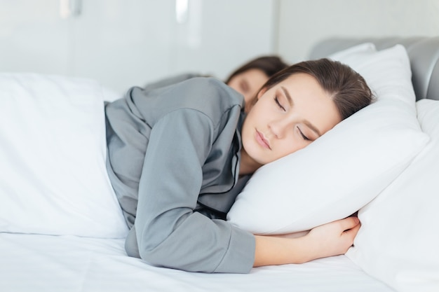 Two pretty young women sleeping in bedroom together