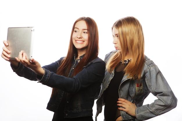 흰색으로 격리된 태블릿으로 자화상을 찍고 있는 두 명의 예쁜 젊은 여성