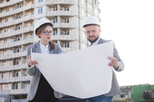 Two professional architect holding blueprint and looking at it near construction site