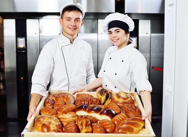 두 명의 전문 베이커-젊고 예쁜 여자와 백인 요리사의 남자