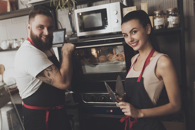 Two professional bakers are standing near oven.