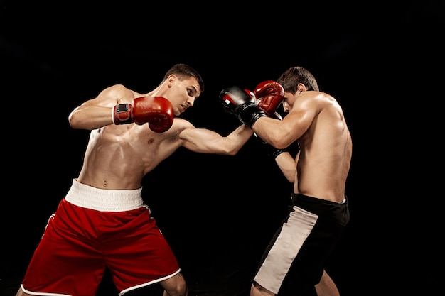 Two professional boxer boxing on black wall