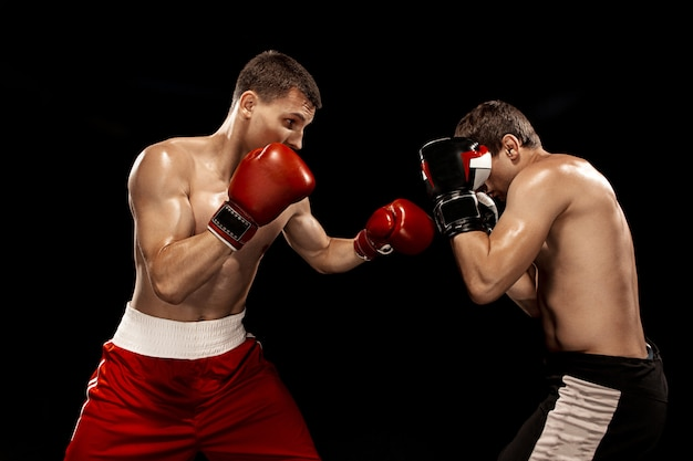 Two professional boxer boxing on black wall,