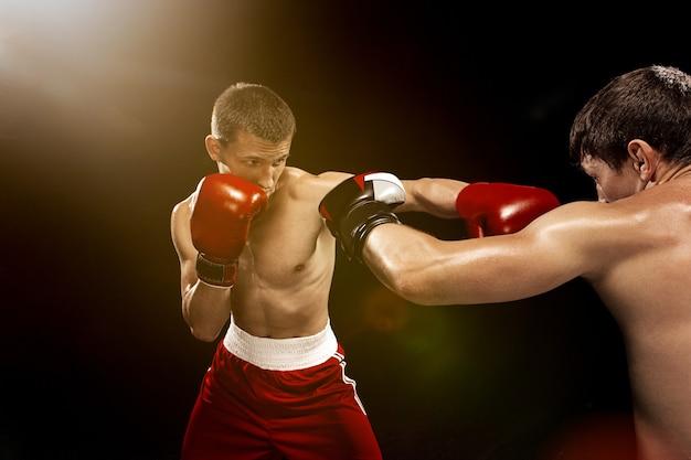 Два профессиональных боксера боксируют на черной стене