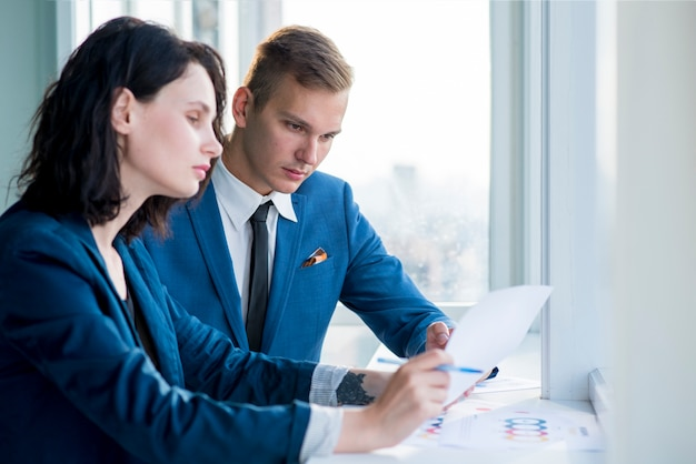 Two professional businesspeople looking at chart in office