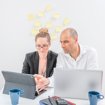 Two professional businesspeople working on laptop in office