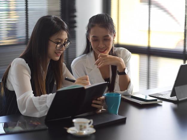 Два профессиональных бизнесвумен обсуждают проект вместе в офисе