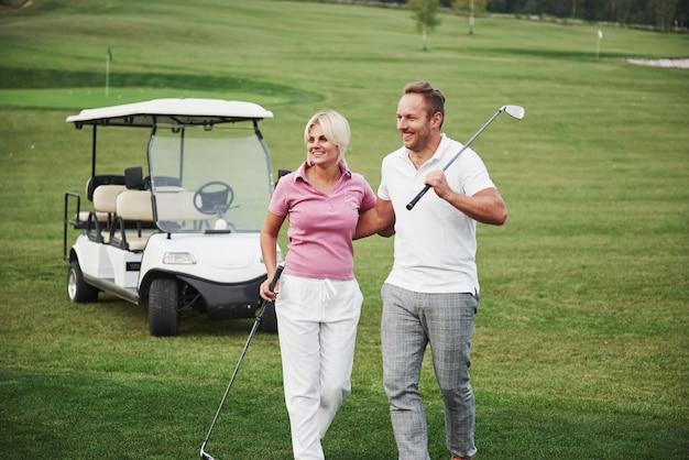 Два профессиональных игрока в гольф, женщина и мужчина вместе отправляются в следующую лунку. влюбленные обнимаются и улыбаются, у них свидание