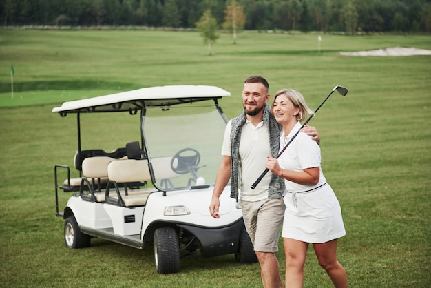 Two professional golfers, a woman and a man go together to the next hole. lovers hug and smile, they have a date