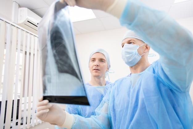 Два профессиональных пульмонолога в защитной форме смотрят на рентген легких и обсуждают его в клиниках