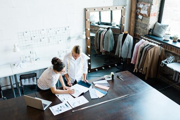Две профессиональные швеи или модельеры обсуждают эскизы новых моделей и образцы тканей на рабочем месте