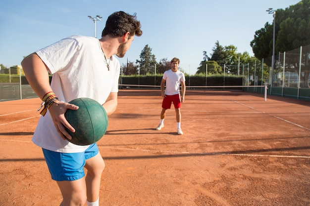 Two professional tennis players warming ub by throwing a medicine ball to each other.