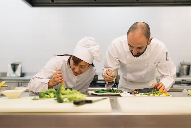 キッチンで一緒に料理をする2人のプロのシェフ。