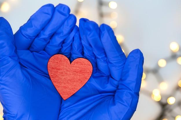 희망 covid-19 및 건강 개념에 대 한 붉은 마음을 잡고 두 보호 파란색 의료 장갑. 코로나 바이러스, 바이러스 및 의료 배경 상위 뷰를 닫습니다.