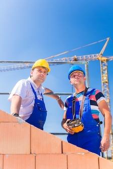 원격 제어로 크레인을 감독하는 집 프로젝트에 서있는 두 명의 자랑스러운 건설 현장 작업자 또는 벽돌공