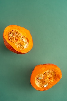 Two pumpkin halves on green background