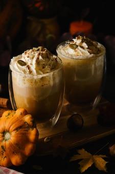 Два тыквенных латте со взбитыми сливками и трубочки в стаканах в стиле dark food. осень горячий пряный напиток на хэллоуин или день благодарения. выборочный фокус