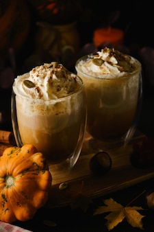 Two pumpkin latte with whipped cream and tubes in a glasses in the style of dark food. autumn hot spicy drink for halloween or thanksgiving. selective focus
