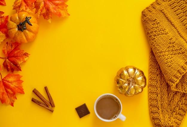 葉メープル、コーヒー、黄色の背景にスカーフと2つのカボチャ。平干し。